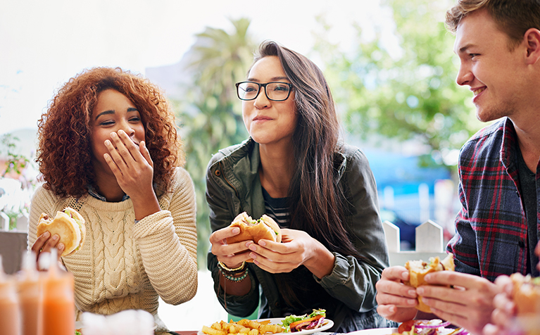 Three people sitting and laughing together while eating hamburgers.